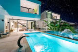 Minimalist modern luxury villa and pool at night