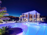 Contemporary luxury glass and white villa and pool at night