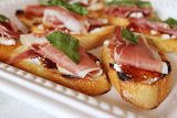 ^ Crostini with goat cheese, prosciutto, fig preserves, basil
