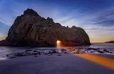 Sun peaking through sea stack Pfeiffer Beach California