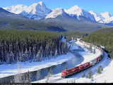 Train Running Through Snow and Ice Covered Mountains
