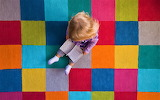 Child on colorful carpet