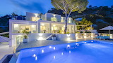 Illuminated luxury white villa and pool at night, Ibiza