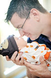 Middle-aged-man-holding-newborn-infant-baby-boy-held-nose-to-nos