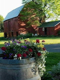 RED BARN AND BARREL OF FLOWERS
