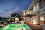 Luxury white bay view villa and pool at sunset