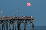 Lots of folks pier fishing under red moon