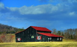 ^ Black barn with a red roof