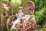 Boy, child, joy, flowers, books, chair, hat, garden, tea party,