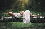 The girl and the fox on the forest glade
