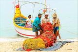 Fishermen carrying heavy nets