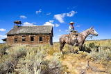 cowboy in front of old wooden house