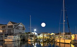 Recreational boats tucked in for night under full moon