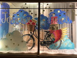 ^ Christmas shop window of bike decorated with multi-coloured wi