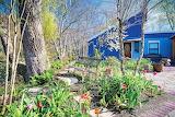 Blue cottage with flower garden in spring