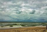 Gray-thunder-clouds-hung-over-baltic-sea-waves-run-onto-sandy-sh