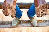 Cowboy legs on wooden fence