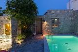 Mediterranean stone courtyard pool at night